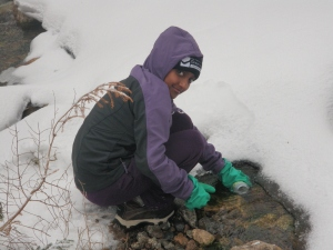 Asha collecting a water sample.